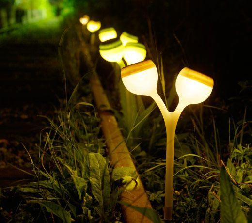 En mörk trädgård med en rad lysande soldrivna LED-markspjut formade som vallmor.