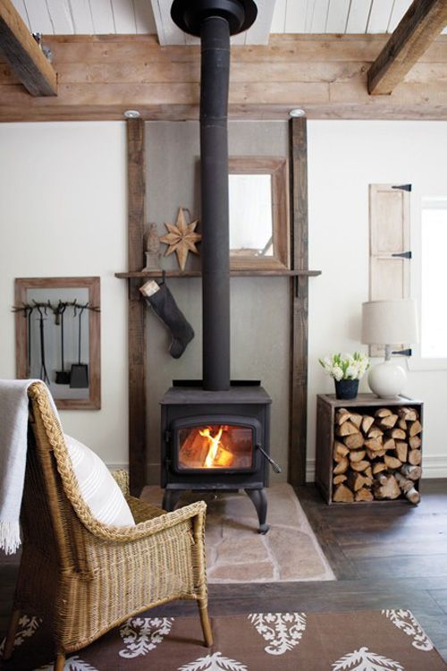 Black woodstove in living room, white walls, stone hearth, hardwood floors. Shelf behind stovepipe and upright beams on each side create illusion of fireplace & mantel, with clean lines. I like the firewood box on its side--cats would love to lie on top of box, so could replace lamp & flowers with a pretty pillow for a cat vignette!