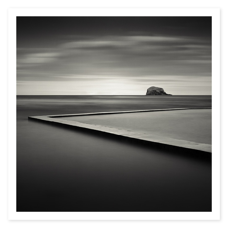 Bass Rock and Tidal Pool. by Colin Homes This was my first shot of the North Berwick tidal pool. It was taken during the day using a 5×7 view camera and a Nikkor 240w lens. I added a six stop neutral density filter and shot the image at f32. This gave me a six minute exposure using Ilford fp4 film. This was long enough to soften the moving clouds and long enough to add contrast to the water as the breaking waves created white streaks in the waters surface.