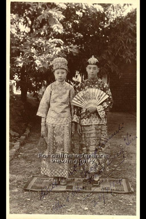 WEDDING COUPLE IN PERANAKAN WEDDING COSTUME TAKEN IN THE 1950S.