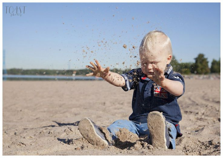 Beach baby portrait. Playing with sand.