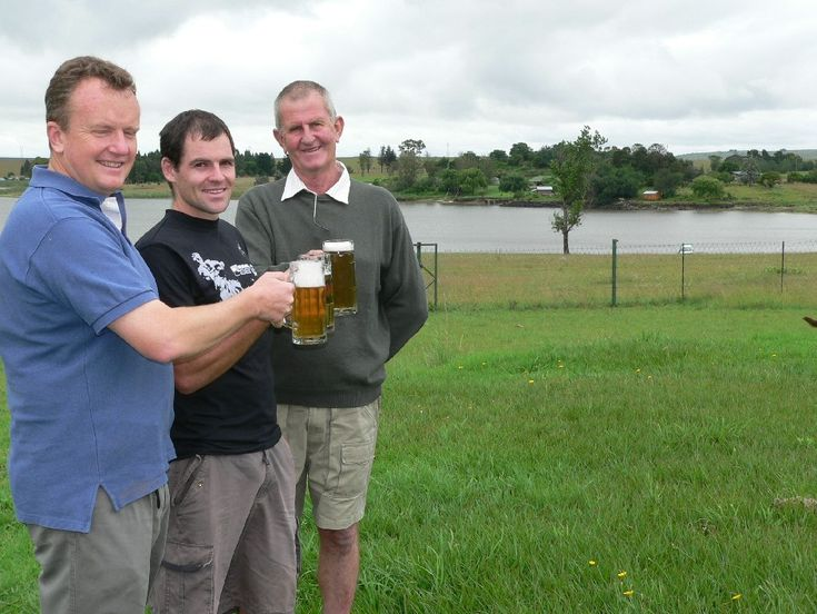 Prost! Sampling the Farmers' Brewery beer and inspecting the level of the Tom Worthington dam are Josef Martin of the Brewery with local athlete, Garren Soutar who surveyed the canoe course and Denis Hodson, father Olympic canoeist, Jen Hodson