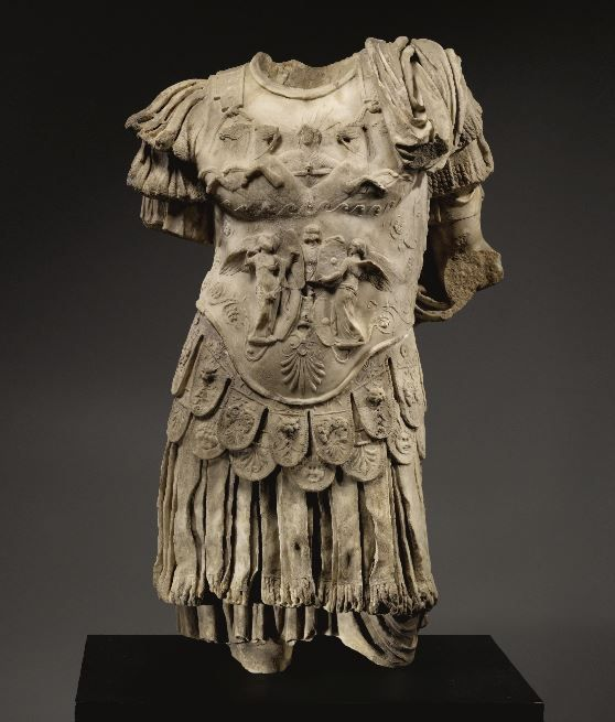 Roman marble torso of an emperor, Roman Imperial, Julio-Claudian, 1st half of the 1st c entury A.D. Carved in two parts, standing with the weight on his right leg and wearing a tunic, leather corselet with fringed lappets falling at the waist, the breastplate decorated in relief on the chest with the god Sol emerging from the waters in a frontal quadriga and on the abdomen with two Victories flanking a trophy and hanging shields, 110 cm high. Private collection