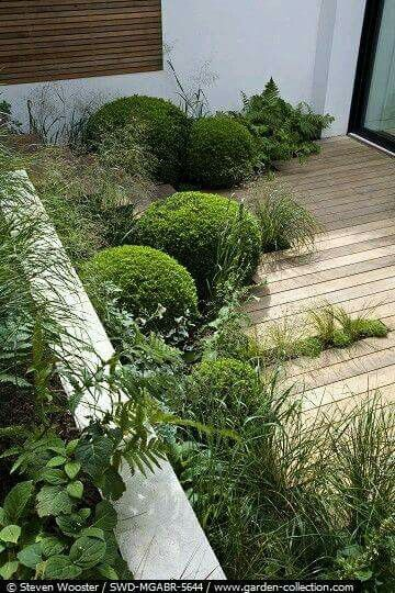 In de scherpe hoek de cottoneaster laten staan, terrasplanken loodrecht op voorgevel leggen, hier en daar inspringen voor groen.