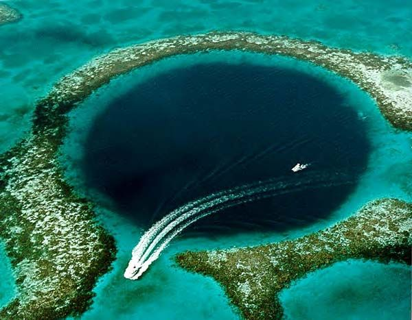 """The """"Blue Hole"""" on Lighthouse Reef in Belize is the entrance to a vast underwater cave. The perfectly circular entrance is wonderfully eerie, and reminds one of similar holes on Mars and on the Moon."""