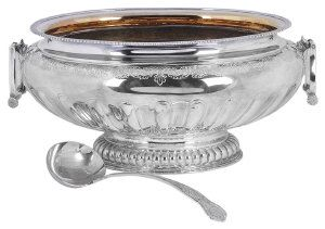 An Impressive Modern Silver Two-Handled Punch Bowl/ Jardiniere, by James Dixon & Sons, Sheffield 1998: In the early 18th century manner, embossed with alternate convex and concave flutes/lobes, flat chased band of trailing acanthus leaves and gadrooned border, angular drop-ring handles, terminating on an oval lobed base, gilt washed interior, length handle to handle 47cm, height 21cm, approx weight 124 troy ounces, together with an electroplated King's pattern soup ladle, (2)