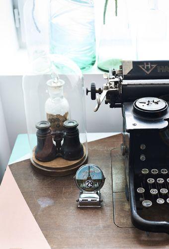 Eine alte Schreibmaschine und ein Fernglas unter HÄRLIGA Glasglocke mit Teller