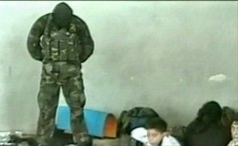 Masked hostage-taker standing on a dead man's switch during the second day of the crisis (a frame from the Aushev tape)