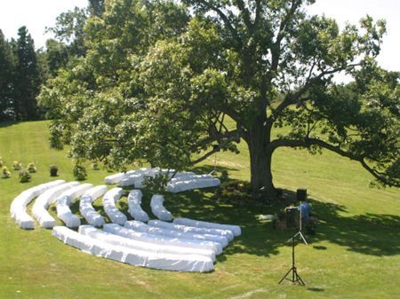 Hay bales covered with white linen for a alternatitive take on ceremony seating