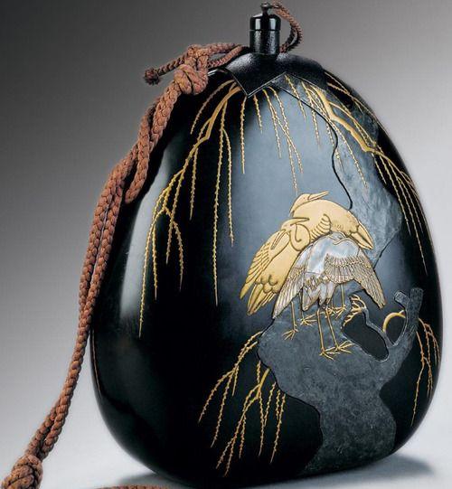 A water flask for use when travelling . wood covered with natural lacquer, decorated with techniques of hiramakie, takamakie, sabiage a raden, inlaid with plumb and furnished with silk cords .   18th Century - 19th Century; around 1800, Japan  Courtesy of the NationalMuseum – the Náprstek Museum of Asian, African and American Cultures, Prague, Czech Republic