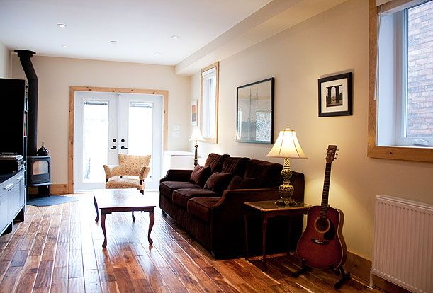 Brock Street Renovation - The living room at the back features two large windows and a pair of french doors leading out to the backyard.  A wood burning stove sits in the corner making the house warm and toasty on cold winter days.