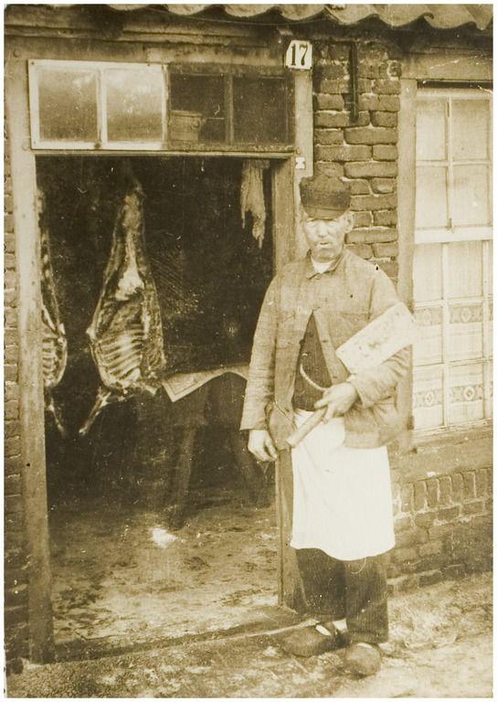 Leonardus van Aarle alias ''Naris den Turk'', geitenslager voor zijn huisje in de Heistraat 17 in Helmond. Achter hem in de kamer enkele geslachte exemplaren, 22-08-1929