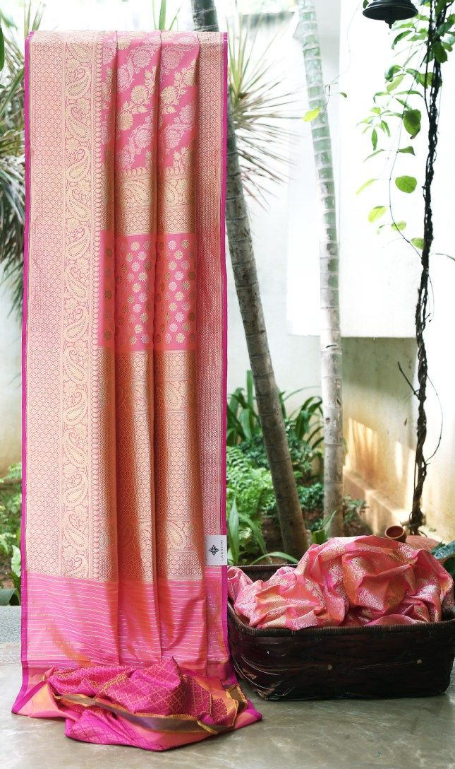 MAGESTIC PASTEL PINK IRIDESCENT PASTEL YELLOW BENARES SILK HAS INTRICATELY WOVEN SPECTACULAR GOLDEN ZARI BORDER AND PALLU. THE PASTEL PINK WITH PURPLE BROCADE BLOUSE MAKES THE SAREE CAPTIVATING.