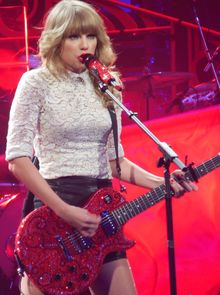A blonde-haired woman holding a sequined red guitar, singing on a stage lit in red and violet