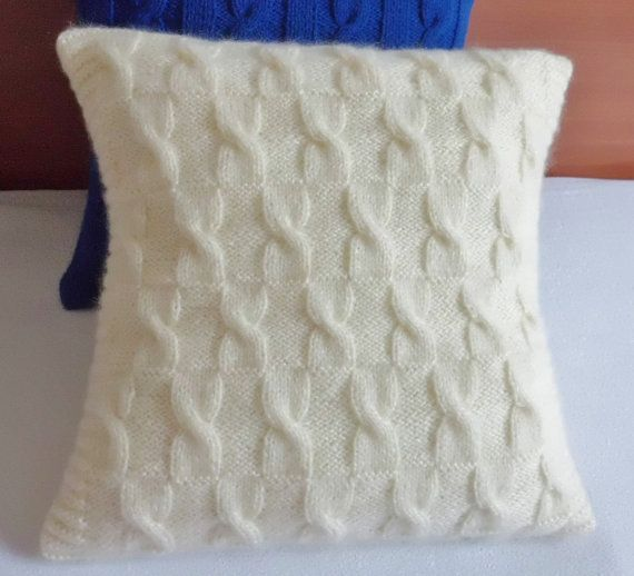 I knitted this pillow cover using a soft ivory color yarn called Angora- Gold. The cushion cover has a cable knit design that resembles bow ties, ans is very soft and cozy.  The design from front continues on back and closes with an envelope style and three crochet buttons.  The pillow would be a perfect addition to a childs room, baby room, or any room with natural or bright colors.    The case would fit a 16 x 16 (40 cm )insert.    Yarn: 20% wool, 20 % mohair, 60 % acrylic.  Lay flat dry…