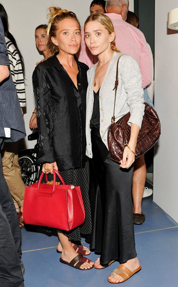 Mary-Kate and Ashley attended the Trademark store opening and dinner wearing similar satin looks with button-down tops, maxi skirts and sandals. Ashley is wearing a bag from The Row.