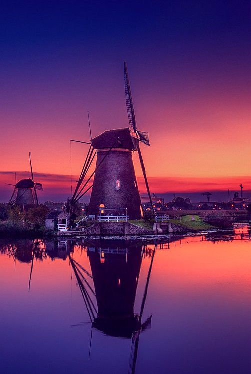 Changing Colors by Herman van den Berge +windmill sunrise, sunset, water, reflection, travel, blue, sun, light, colored, gold, colors, mill, windmill, dutch, blue hour, golden.