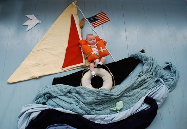 This is beyond adorable.  The baby is on the ground and the boat is made of blankets.  So creative!