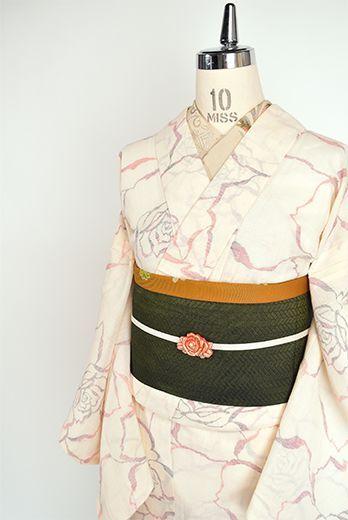 生成り色の地に、ローズレッド、スカーレットオレンジ、コーラルピンクなどの色糸で織り出された薔薇の花のモチーフが物語をさそう夏紬風の夏着物です。