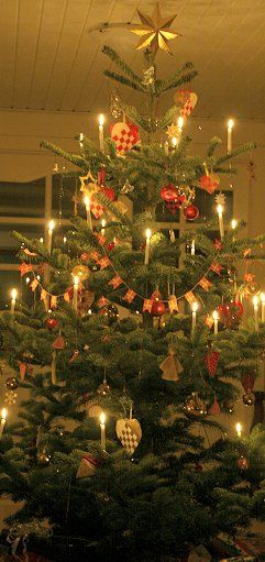 Christmas tree, decorated in traditional danish style: folded hearts, candlelights and tiny red & white flags.