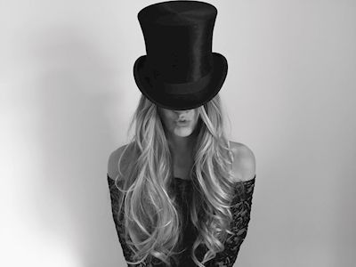 Jennie Antunovic  - Hatt. A black and white photograph of a woman with long blonde curls wearing a black top hat.
