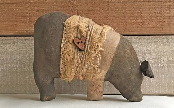 Primitive pot-bellied pig tuck is perfect for the bookcase, cupboard, shelf, or display as basket and bowl fillers. The Hampshire pig is painted with acrylics, sprinkled with cinnamon and spices, and then made to look old and worn. The pig is wrapped with prim-stained cheesecloth and