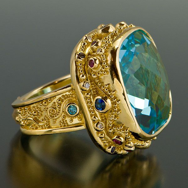 Ring is set with a Blue Topaz, Blue Sapphires, Hot Pink Sapphires, Diamonds and Blue Zicons in granulated 22kt yellow gold with an 18kt yellow gold inner sleeve.