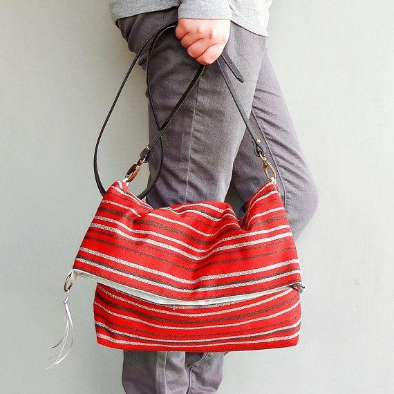 Borsa foldover convertibile che può essere utilizzato come un messenger bag, borsa a tracolla o borsa. In favoloso Baja hippy stile tappezzeria tessuto con strisce profondo marrone e grigi su sfondo rosso ricco. Questo tessuto è un grande omaggio alla meravigliosa Baja Hoodies, ma molto più robusto e durevole.  Comprende un 1 cuoio fibbia Cinturino personalizzato taglio da 21 (per una calzata più stretta sotto il braccio) a 54(per plus sized postino o da appendere basso dellanca) e snella…