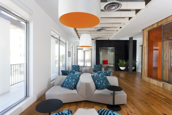Ultra modern lighting fixtures with orange interior provide definition of space for this lounge area at Innocean Worldwide Advertising.  By Kenneth Brown Design.