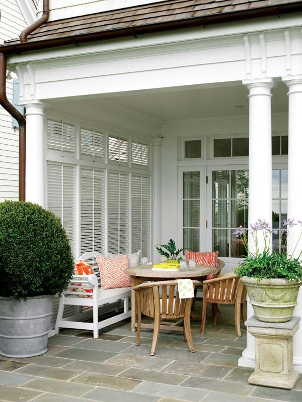 comfy outdoor nook with an over-sized boxwood, stone tile, and quadrille pillows.
