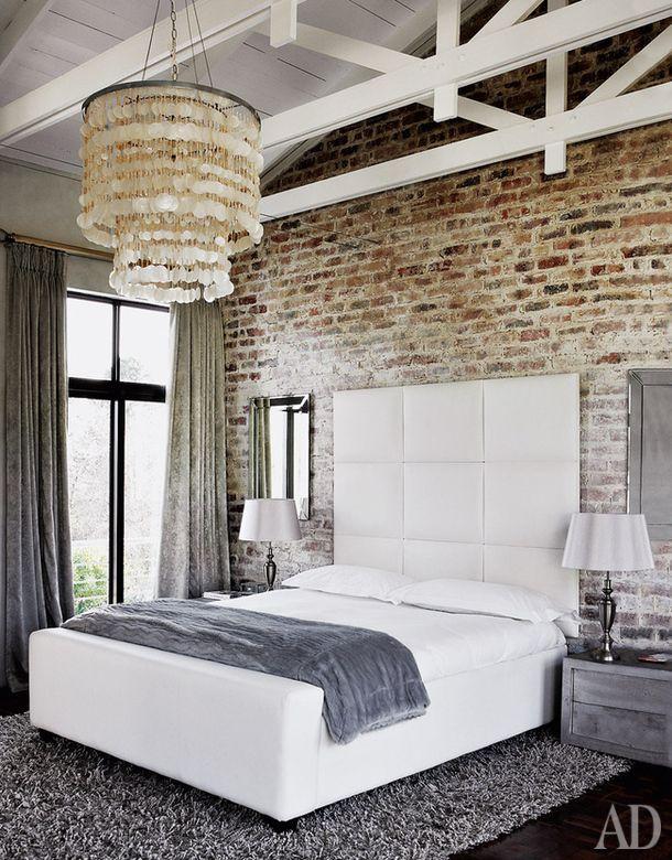 """Спальня сделана по принципу """"противоположности притягиваются"""": фоном для изящной люстры и белой кровати стала брутальная кирпичная кладка. Место действия — Претория, ЮАР."""