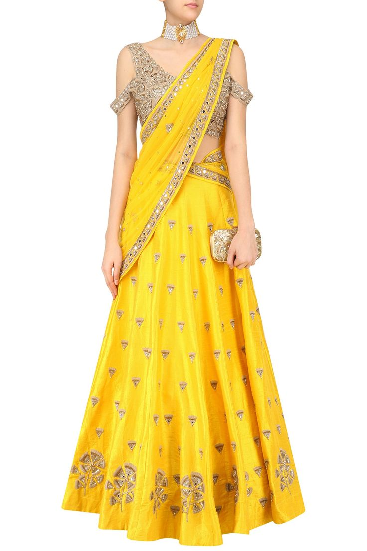 a yellow lehenga with gingko embroidery all over. It comes along with a short sleeve open shoulder gingko embroidered blouse and a yellow net dupatta with embroidered borders.