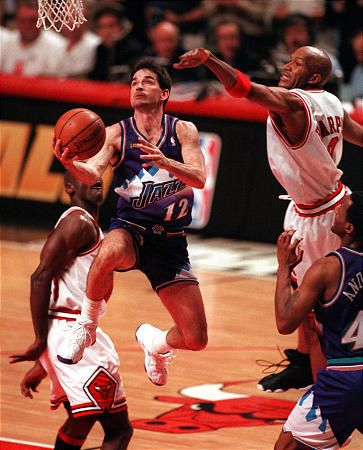 John Stockton drives past the outstretched arm of Chicago's Ron Harper as Michael Jordan, left, watches during Game 4 of the NBA Finals in Chicago on Wednesday, June 10, 1998. (Chuck Wing, Deseret News)