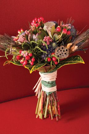 Blue eringium, pink rice flowers and red hypericum berries provide a range of texture and color in a Walter Knoll Florist bouquet hand-tied in raffia showcasing a natural theme to its very roots. Nestled amid dried wheat, lotus pods and peacock feathers, its random look turns lush with flat-leafed lukadendron amid flowery plants and yellow-defined croton leaves defining the edge. |  stlouisbestbridal.com