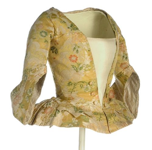 """Casaca Rococo , ca. 1750-1760 Lampas silk jacket in yellow with floral polychrome decoration . Long to the hip, cut at the waist and pleats on the sides. The skirts are decorated with simulated portfolios pockets. The sleeve, with around three quarters sleeve  Structurally matches the dress coats in use in the eighteenth century, Juan de Albayceta collected in his books of patterns 1720. Large laps manga , called in Spain """" sleeves boot"""" ,"""