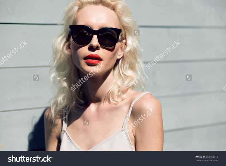 Close up portrait of a beautiful blonde woman in sun glasses posing outside with wooden wall in background. Fashion accessories. Make up and beauty concept