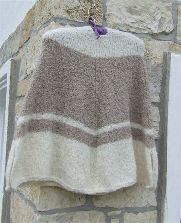 Lovely soft knitted hooded poncho in cream and beige with small slits at the sides for ease of arm movement Knitted in Drops Alpaca Boucle yarn which gives a textured uneven stitch pattern Very soft cuddly yarn   Size - 24 (61 cm) length x 22 (56 cm) at neck opening 52 (132 cm) at middle and 68 (173 cm) at bottom (around) hood approx 14 (36 cm) long   Material - 15% wool, 80% Alpaca 5% polyamide Would fit up to a UK size 14 (US 10 European 42) Sits around hip length   Colour may appear…