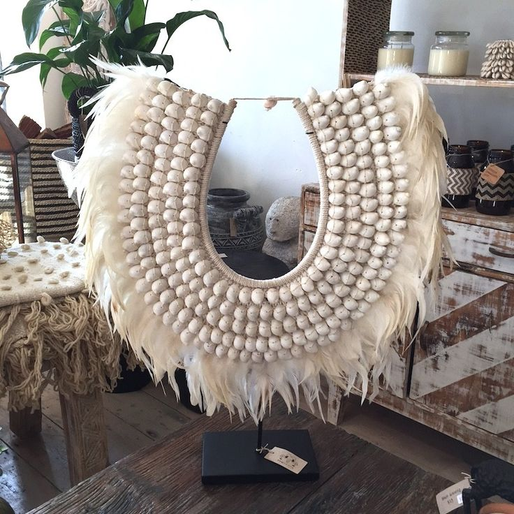 Beautiful papua tribal neck piece. Hand made with shells and white feathers. Comes with a black stand. 65cm width. 55cm height. when on stand becomes 65cm height.