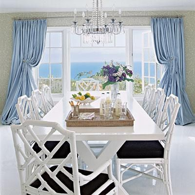 Blue curtains frame the spectacular view in this dining room.