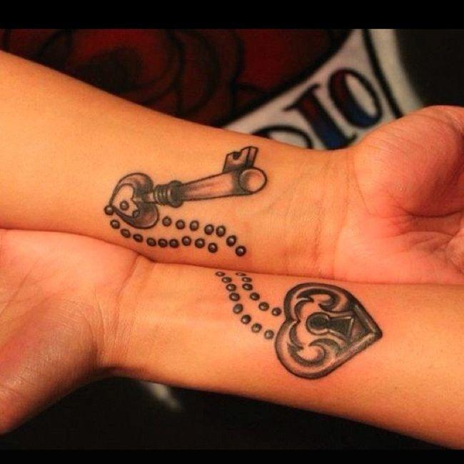 Bazos de una pareja mostrando en sus muñecas sus tatuajes en forma de cadena y corazón