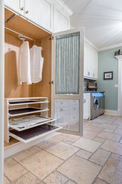 drying racks tucked away in a screened airing closet in this light-filled laundry room