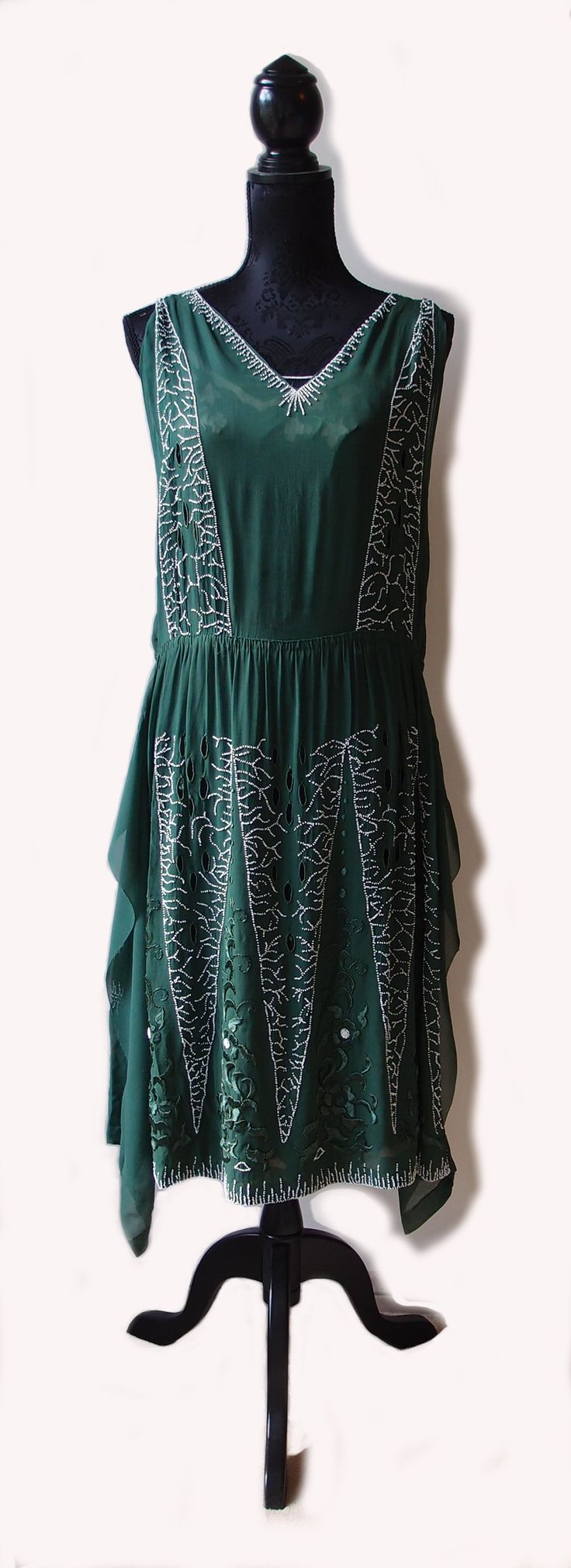 Early 1920s green dress by Jeannetton of New York. Handkerchief hem, floral embroidery and white beading. Dress has been altered/shortened by gathering at the natural waist.