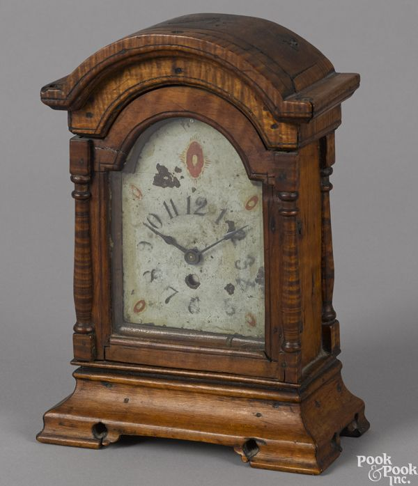 "Pennsylvania tiger maple shelf clock, late 18th c., with a later key wind-up movement and the original painted tombstone face, 9"" h. Provenance: Titus Geesey.  Estimate: $1000–$1500  Realized Price: $6100 Condition: Good condition. Lacking finials."