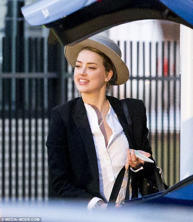 Delighted: on Sunday, Johnny Depp's ex wife, Amber Heard looked the picture of content as she boarded the Tesla boss' private jet to fly out of Sydney