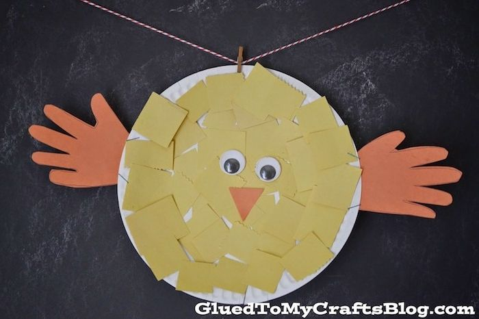 easter crafts for preschoolers, chick ornament made from round, white paper plate, covered in yellow pieces of paper, with orange hand-shaped cutouts for wings