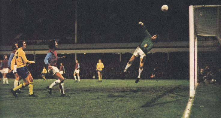 23rd November 1971. West Ham United goalkeeper Bobby Ferguson making a flying save from Uwe Seeler who was playing for a European XI in Geoff Hurst's Testimonial, at Upton Park.