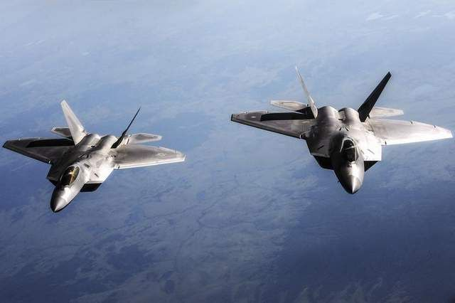 Two Air Force F-22 Raptor aircraft fly behind a KC-135 Stratotanker aircraft. Twelve F-22s and about 300 personnel from Joint Base Langley-Eustis, Va., are deploying to Kadena Air Force Base, Japan. (Senior Airman Zachary Perras / Air Force)