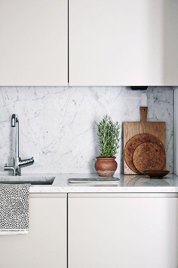 Köksluckor i beige, bänkskiva och stänkskydd i marmor