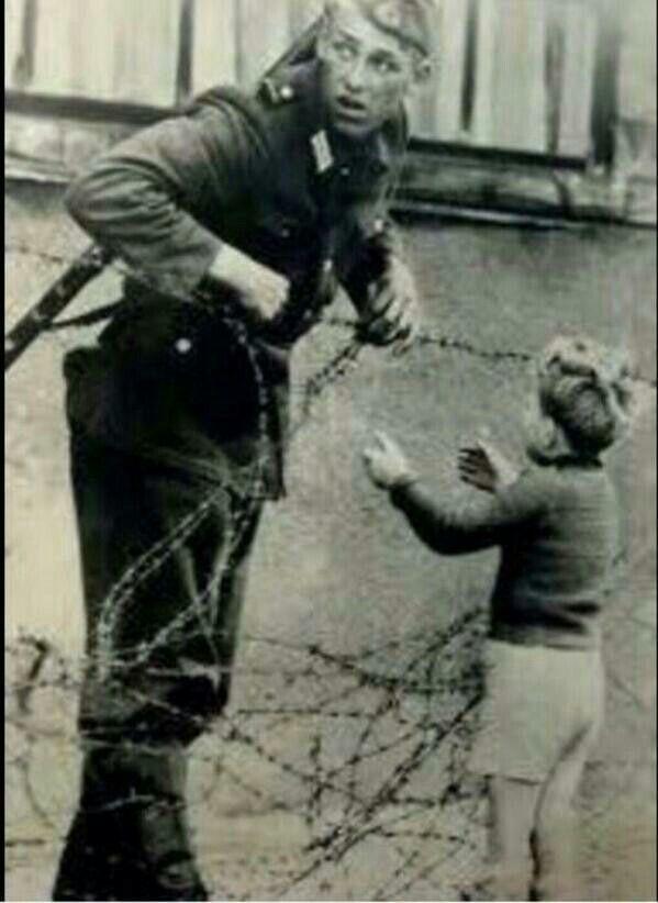"""صورة لجندي يفتح السلك الشائك في جدار برلين لطفل ليلحق بأهله. الجندي اعتُقل واعدم ! """"احيانا تكون جريمتك انك انسان"""" ~ za"""