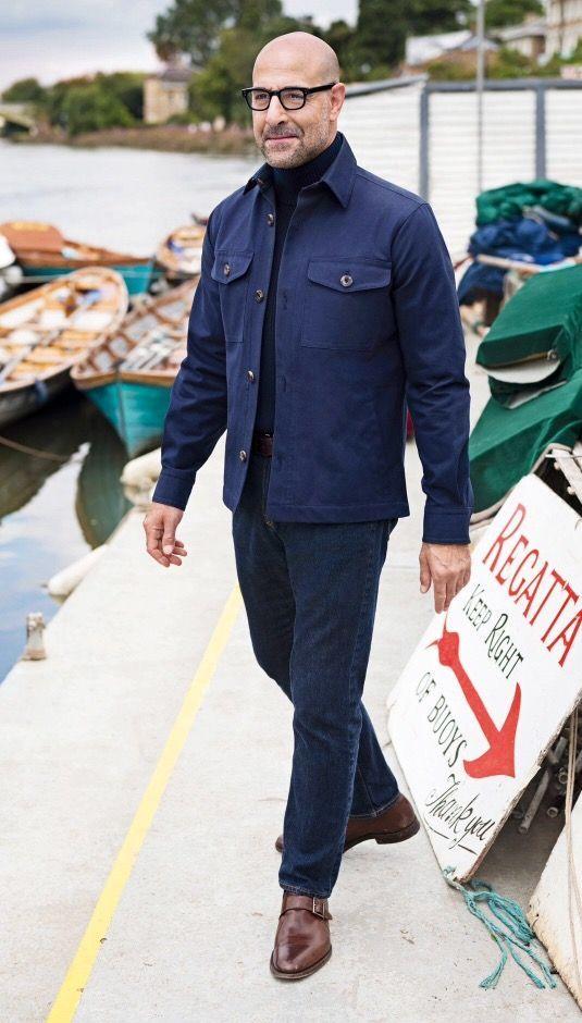 Stanley Tucci portant des lunettes noirs, un pull à col roulé bleu mariné et une veste d'inspiration workwear #style #menstyle #streetstyle #bald #men #glasses #sweater #workwear #look #mode #homme #chauve #stanleytucci